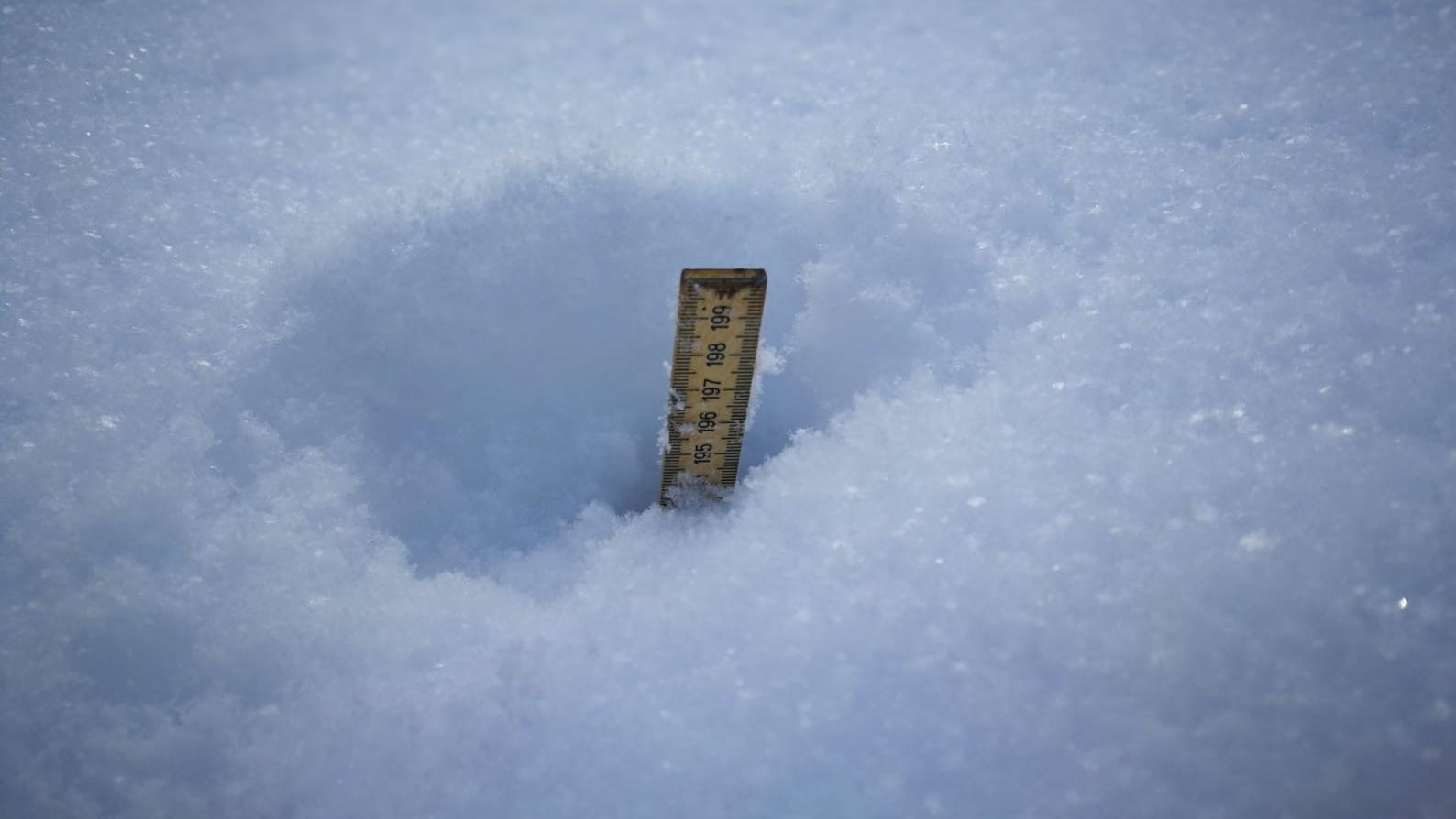 Ein Metermaß versinkt im Schnee.