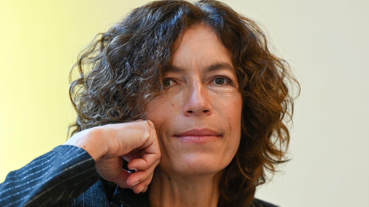 Die Autorin stützt das  Gesicht auf ihre Hand