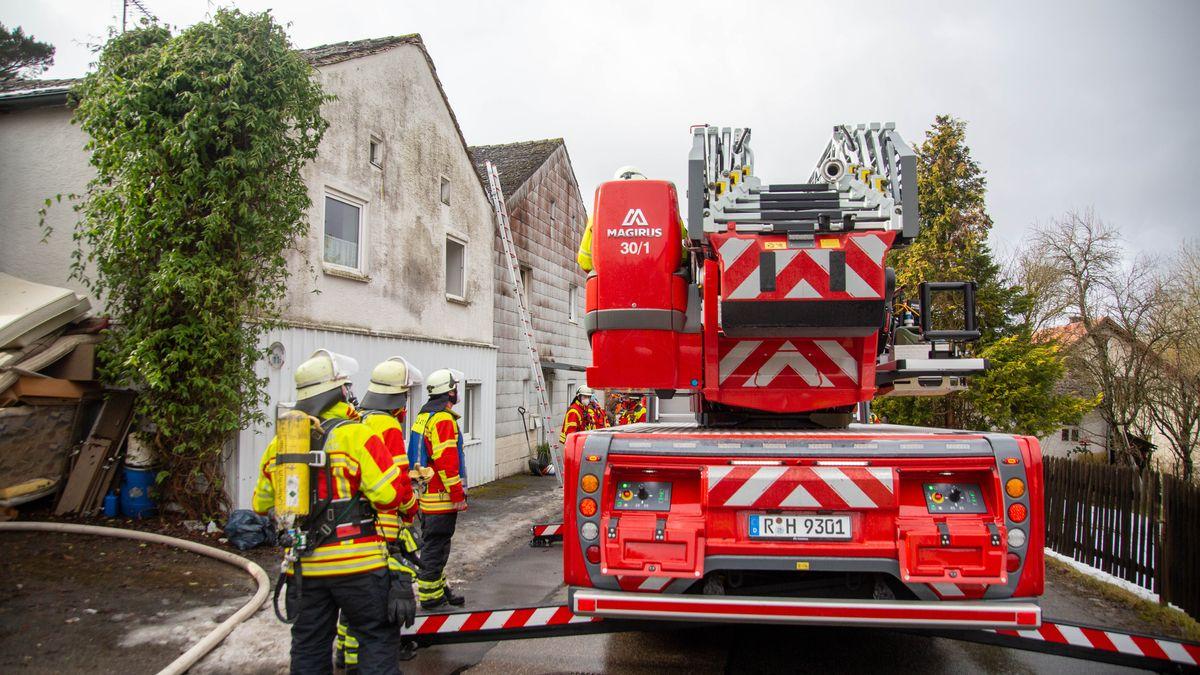 Ein Einsatzfahrzeug der Feuerwehr steht vor einem Haus.
