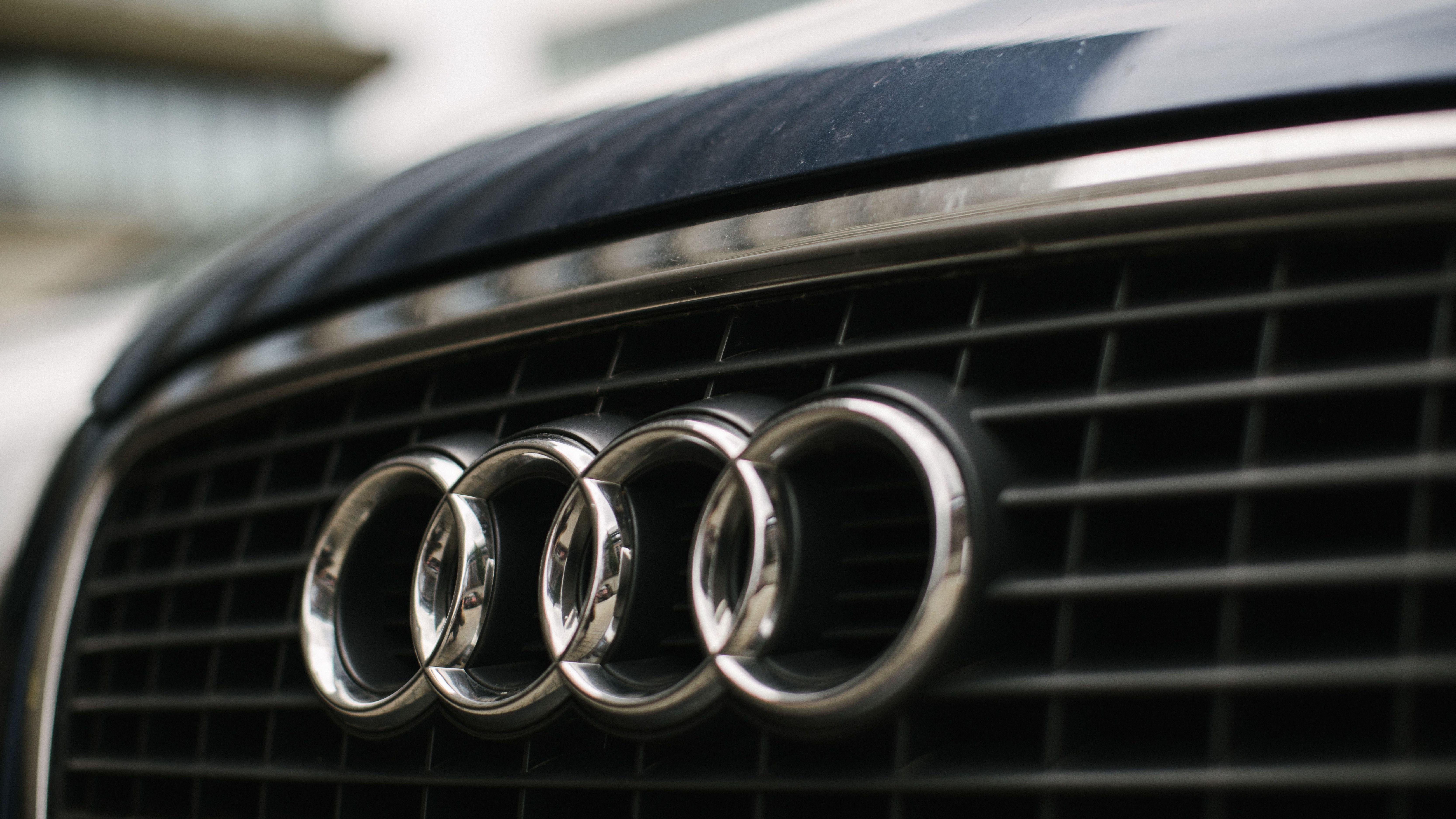 Das Audi-Firmenlogo am Kühlergrill eines Autos