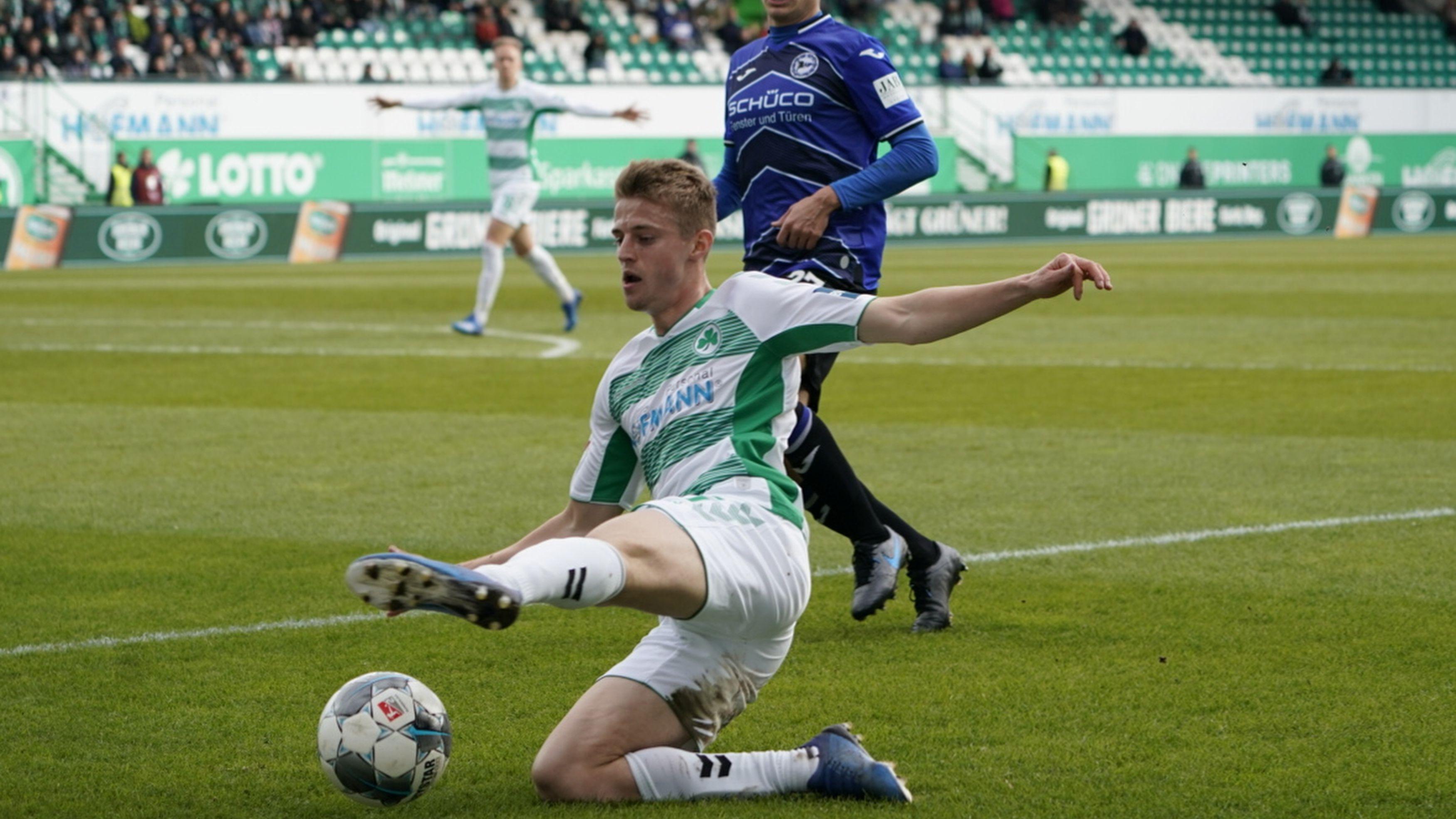 Der Fürther Sebastian Ernst grätscht nach dem Ball, am Ende unterliegt er den Bielefeldern.