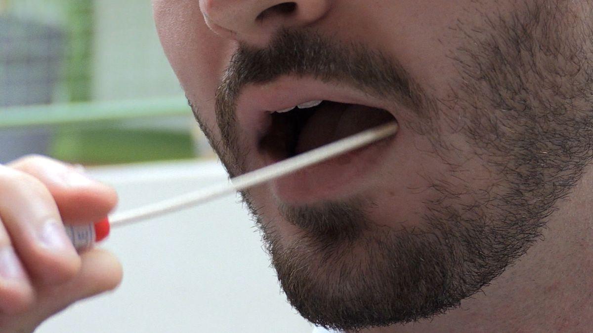 Ein Mann nimmt mit einem Stäbchen eine Probe aus seinem Mund