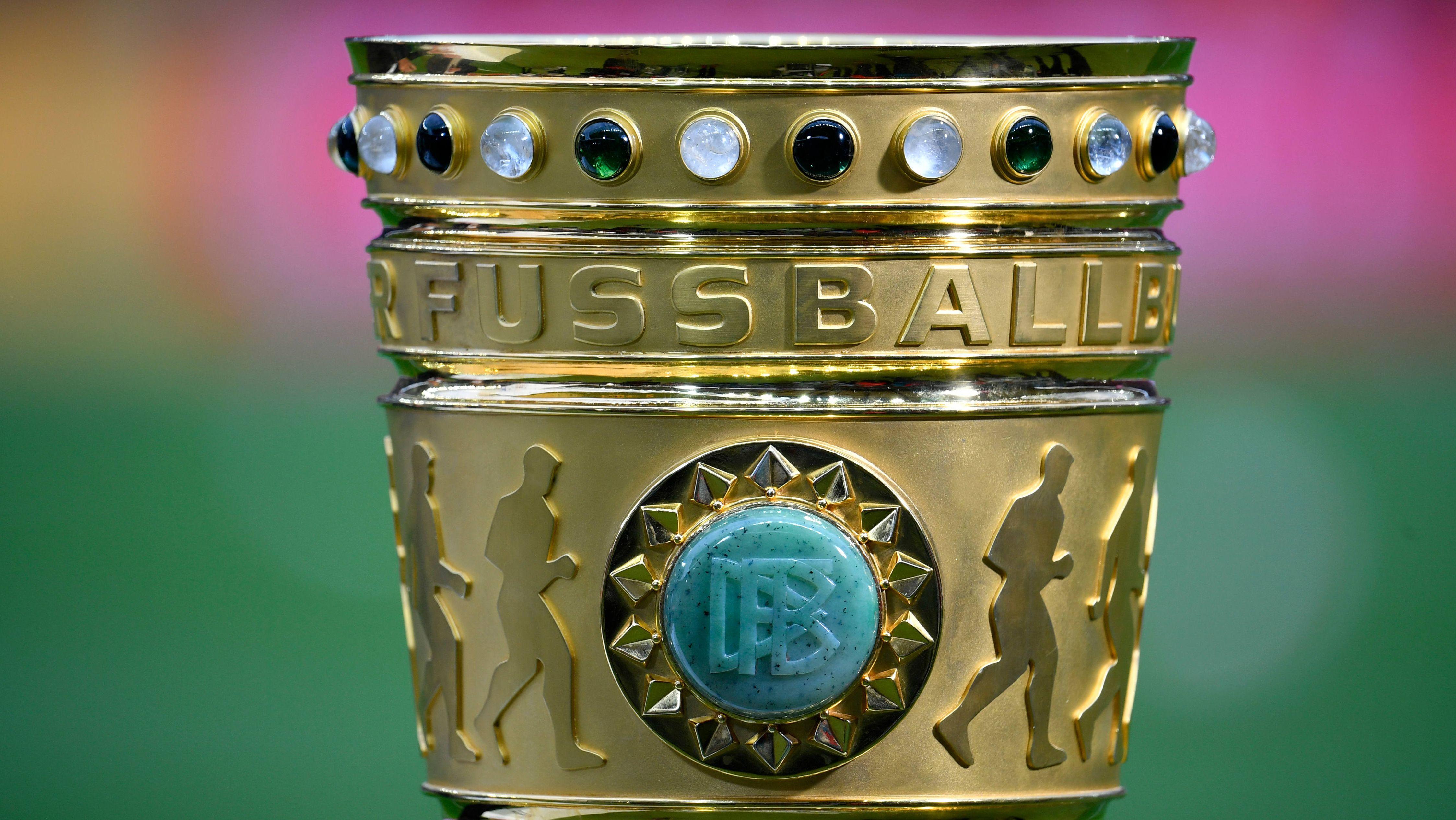 Der DFB-Pokal steht am Spielfeldrand.