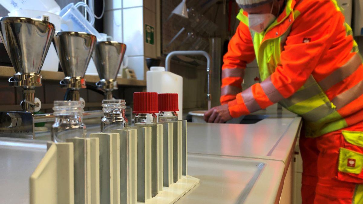 Im Klärwerk Berchtesgaden ein Mitarbeiter steht im Laborraum im Vordergrund Proben von Abwasser.