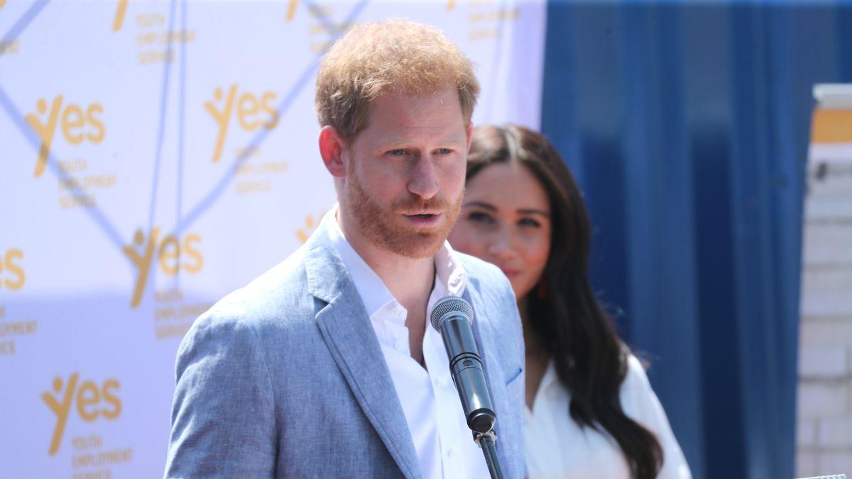 Prinz Harry vor einem Mikrofon bei einer Pressekonferenz, daneben seine Frau Meghan
