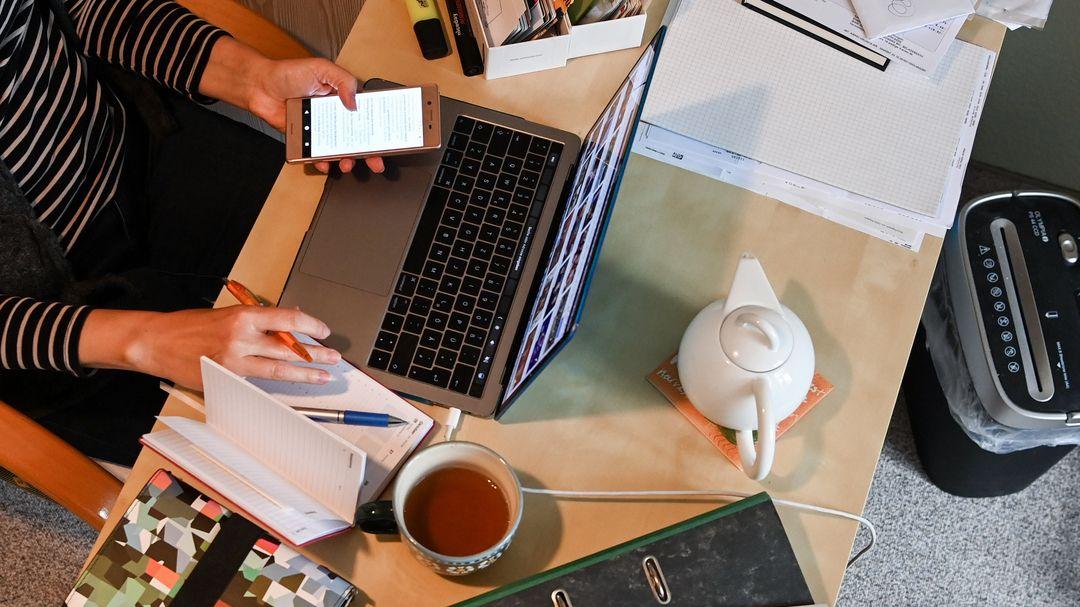 Eine Frau sitzt im Homeoffice am Computer, schaut in ihr Handy und hat eine Tasse Tee vor sich auf dem Schreibtisch stehen.