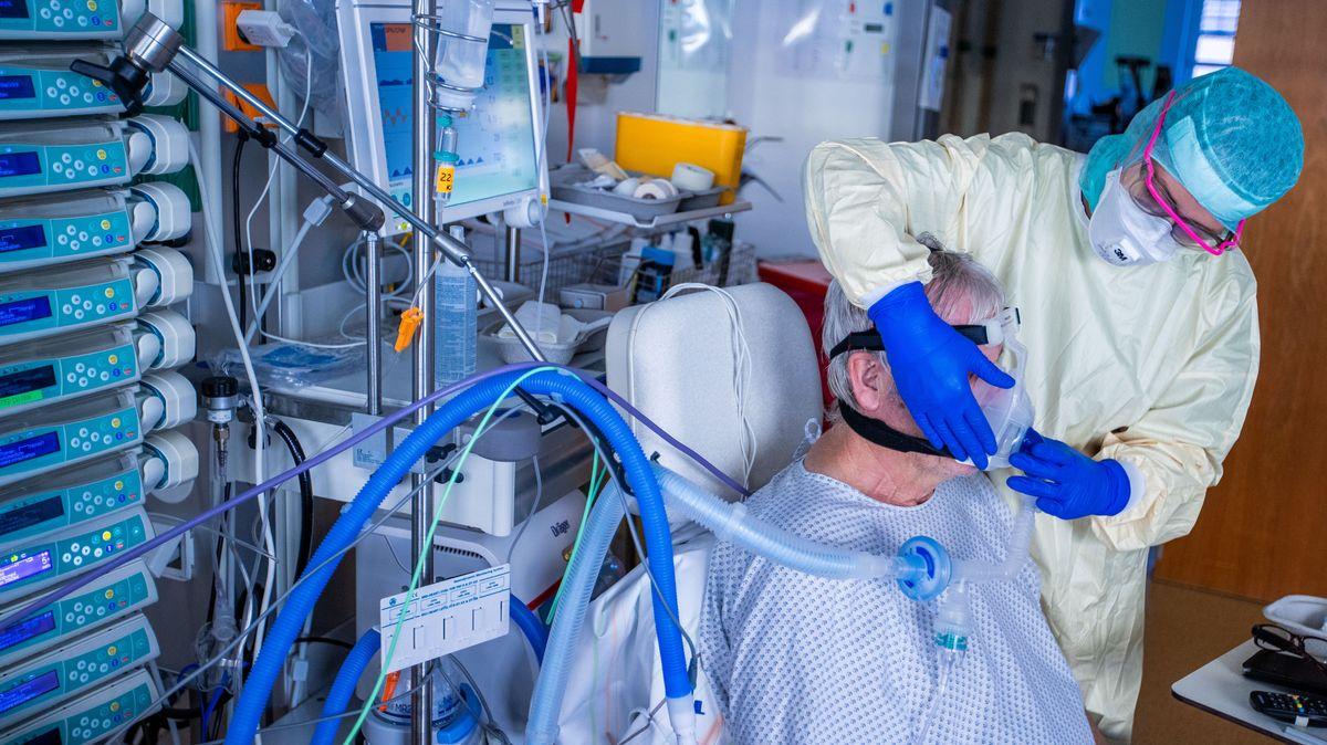 Eine Krankenschwester in Schutzkleidung mit einem Patienten auf der Intensivstation.