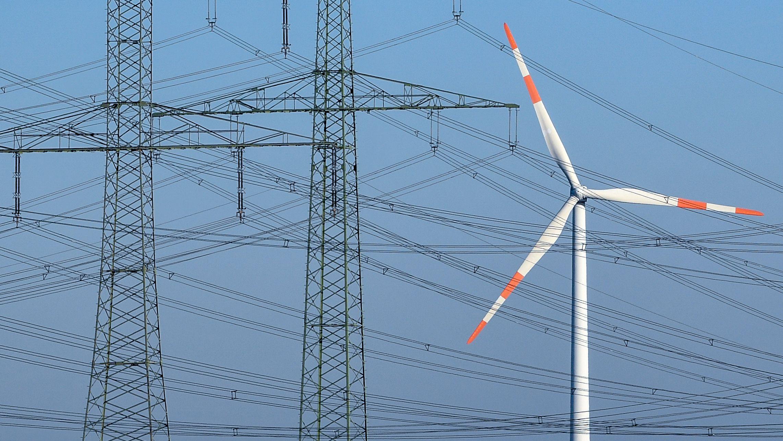 Windkraftanlage vor Strommasten