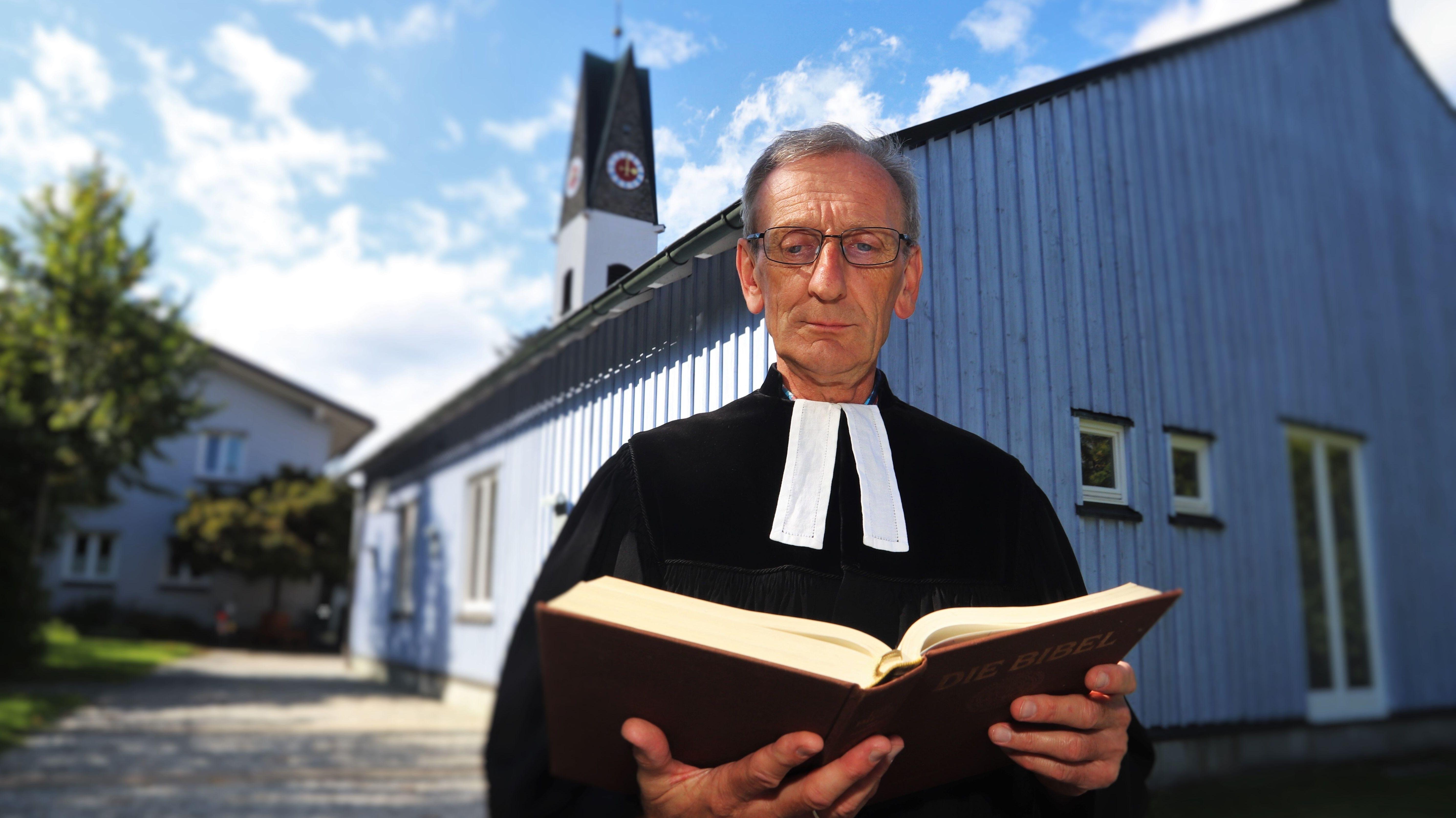 Pfarrer Ulrich Gampert mit aufgeschlagener Bibel in den Händen, im Hintergrund ist der Kirchturm der evangelischen Kirche in Immenstadt zu sehen.