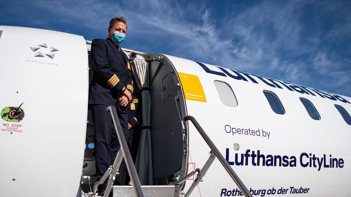 Ein Lufthansa Flugkapitän steht am Flughafen Münster-Osnabrück an der Tür einer Lufthansa CityLine Maschine.