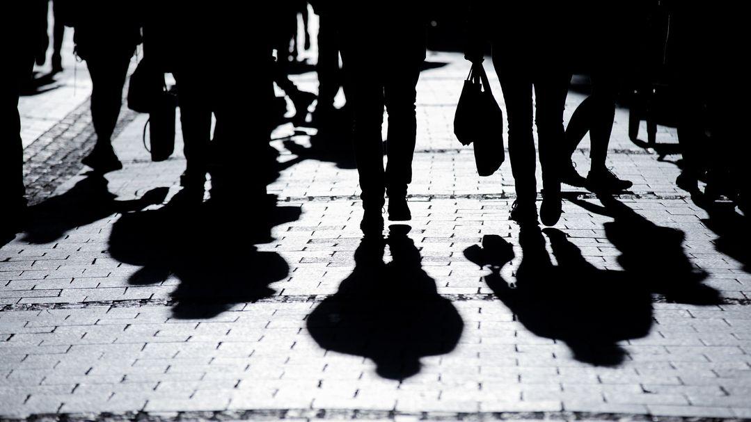 Mehrere Menschen werfen Schatten auf ein Straßenpflaster in einer Stadt
