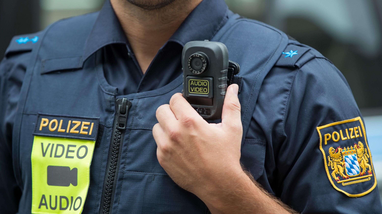 Ein Polizist präsentiert eine Body-Cam.