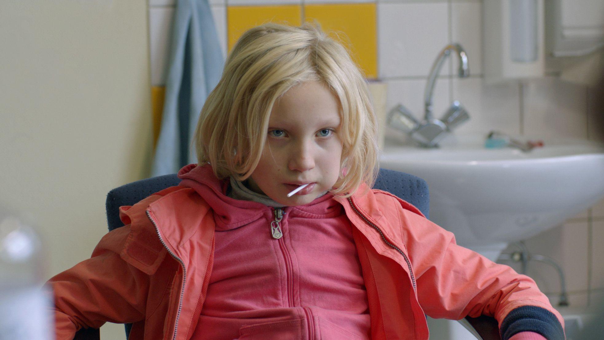 """Szene aus """"Systemsprenger"""": Schauspielerin Helena Zengel hat einen Lolli im Mund und blickt aggressiv an der Kamera vorbei"""