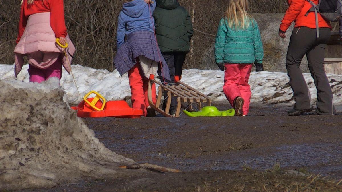 Kinder und Erwachsene auf der Suche nach letzten Schneeflecken zum Schlittenfahren.