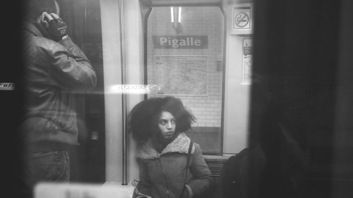 """Eine Frau sitzt in der U-Bahn, blickt nach links, hinter ihr das Schild der Station: """"Pigalle""""."""