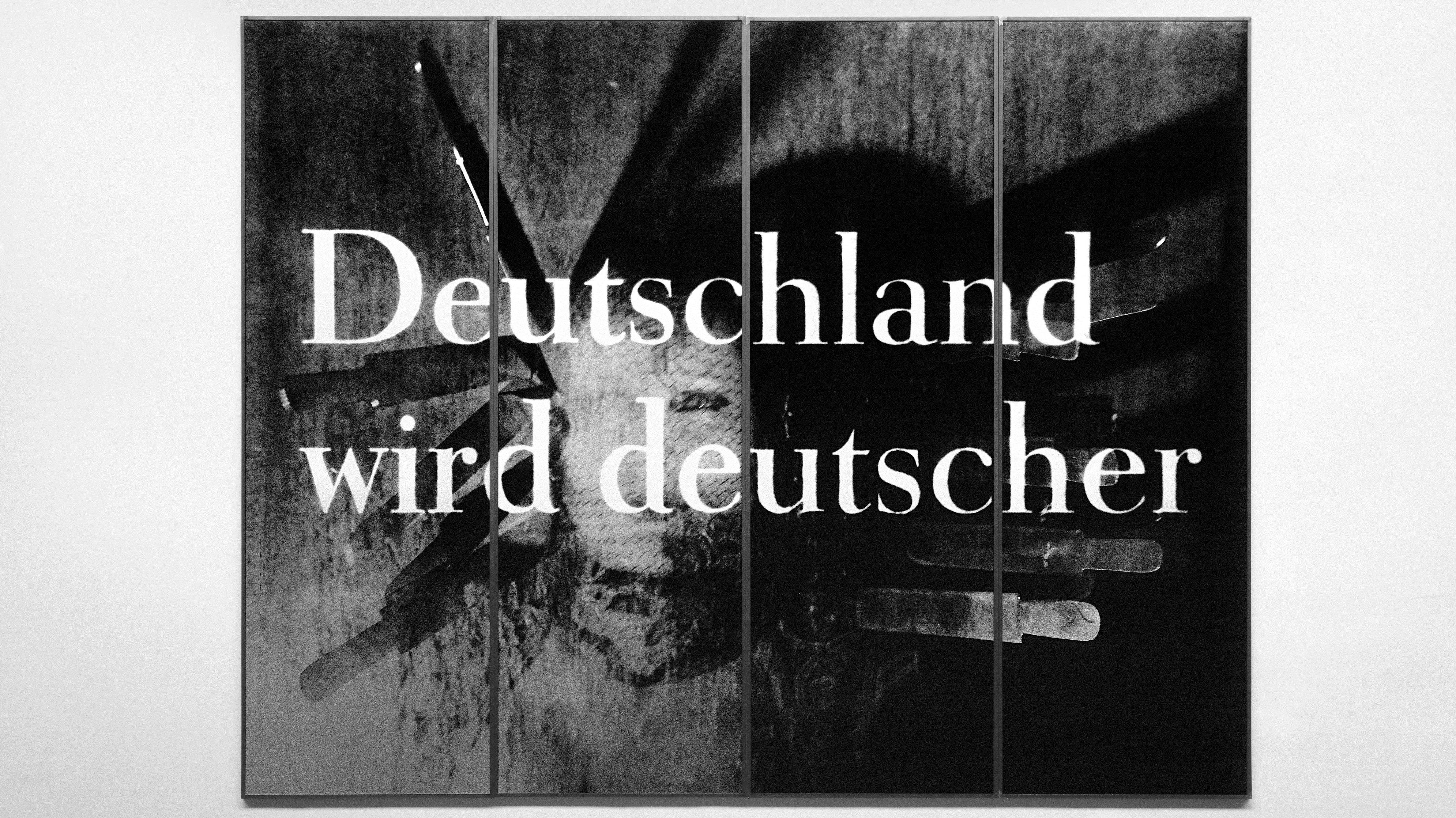 """PLakat """"Deutschland wird deutscher"""" von Katharina Sieverding: Schrift auf einem Foto mit Kopf vor einer Messerwerferwand"""