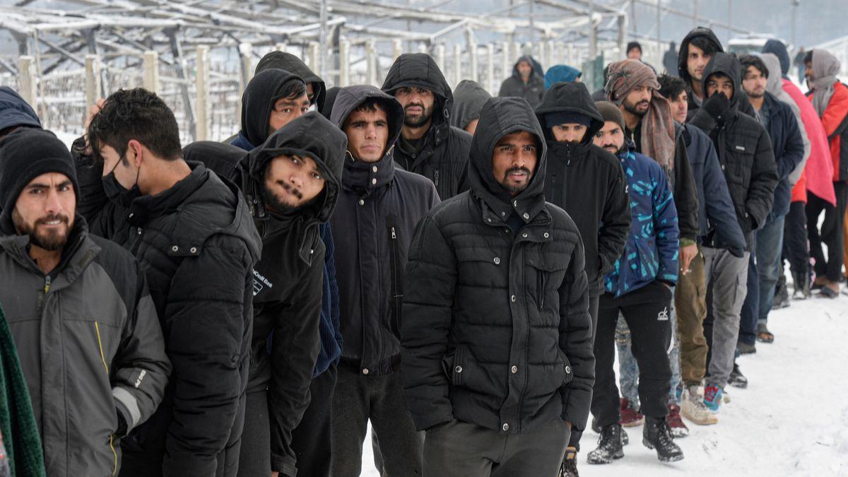 Migranten warten in einer Schlange