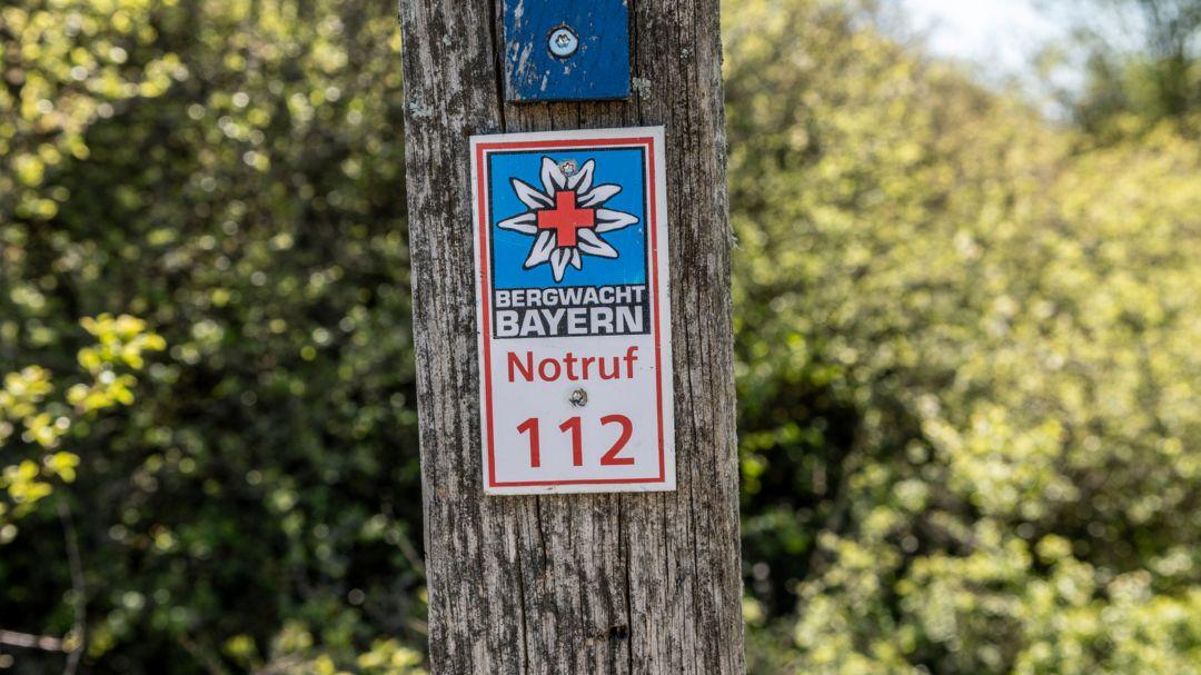 """""""Bergwacht Bayern; Notruf 112"""" steht auf einem Schild"""
