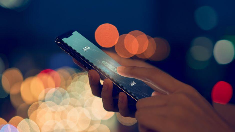 Eine Frau hält ihren Finger auf das Touchfeld ihres Smartphones, um ihr Smartphone per Fingerabdruck zu entsperren.