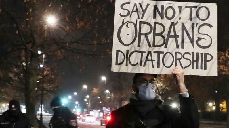 Ein Mann hält ein Plakat hoch, dass Ministerpräsident Orbán als Diktator bezeichnet.