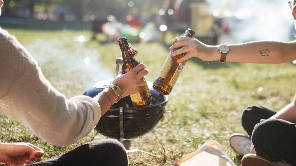 Zwei Freundinnen stoßen im Park mit einem Bier an