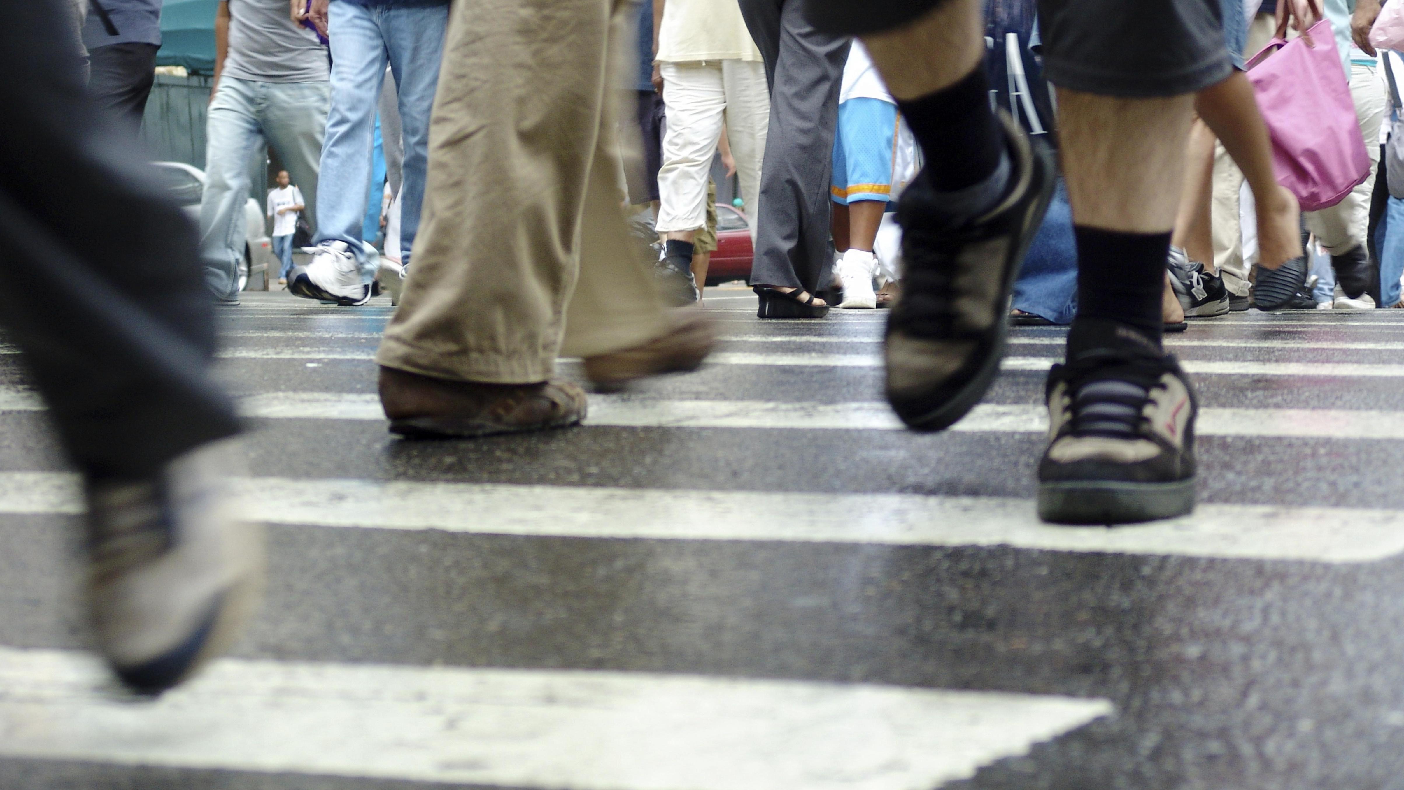 Fußgänger überqueren eine Straße auf einem Zebrastreifen.  Das Umweltbundesamt fordert mehr Maßnahmen für Fußgänger im Straßenverkehr.