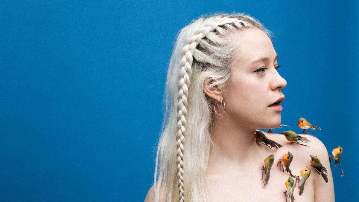 Blonde, junge Frau mit geflochtenen Zöpfen schaut, den Kopf nach rechts gewandt, in ferne Zukunft. Auf ihrer rechten Schulter sitzen Kanarienvögel.