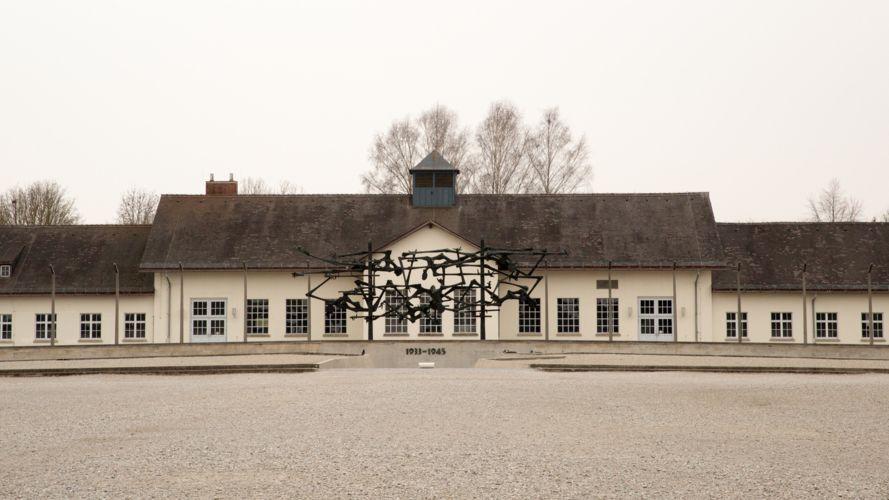 Ansicht auf die Gedenkstätte des Konzentrationslagers Dachau, im Vordergrund ein leerer Platz, vor dem Hauptgebäude eine Skulptur.