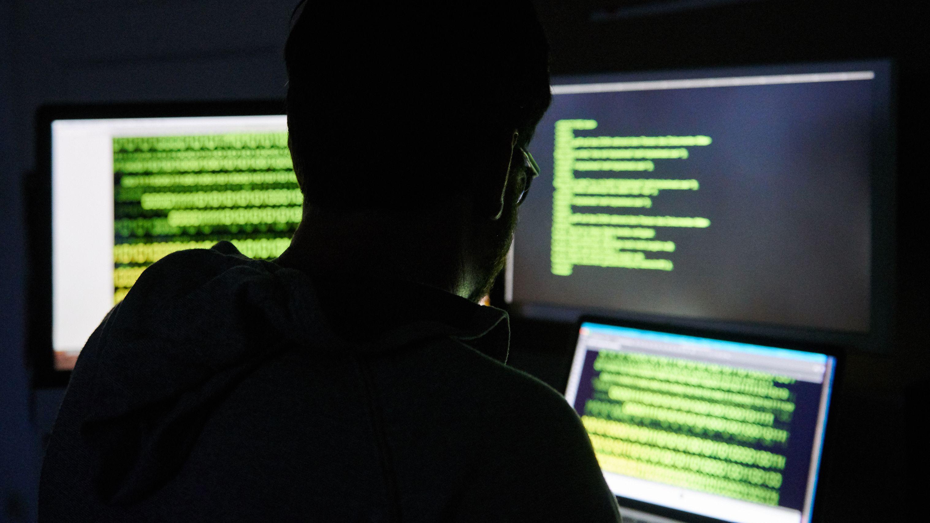 Ein Hacker sitzt im Dunklen vor Bildschirmen.