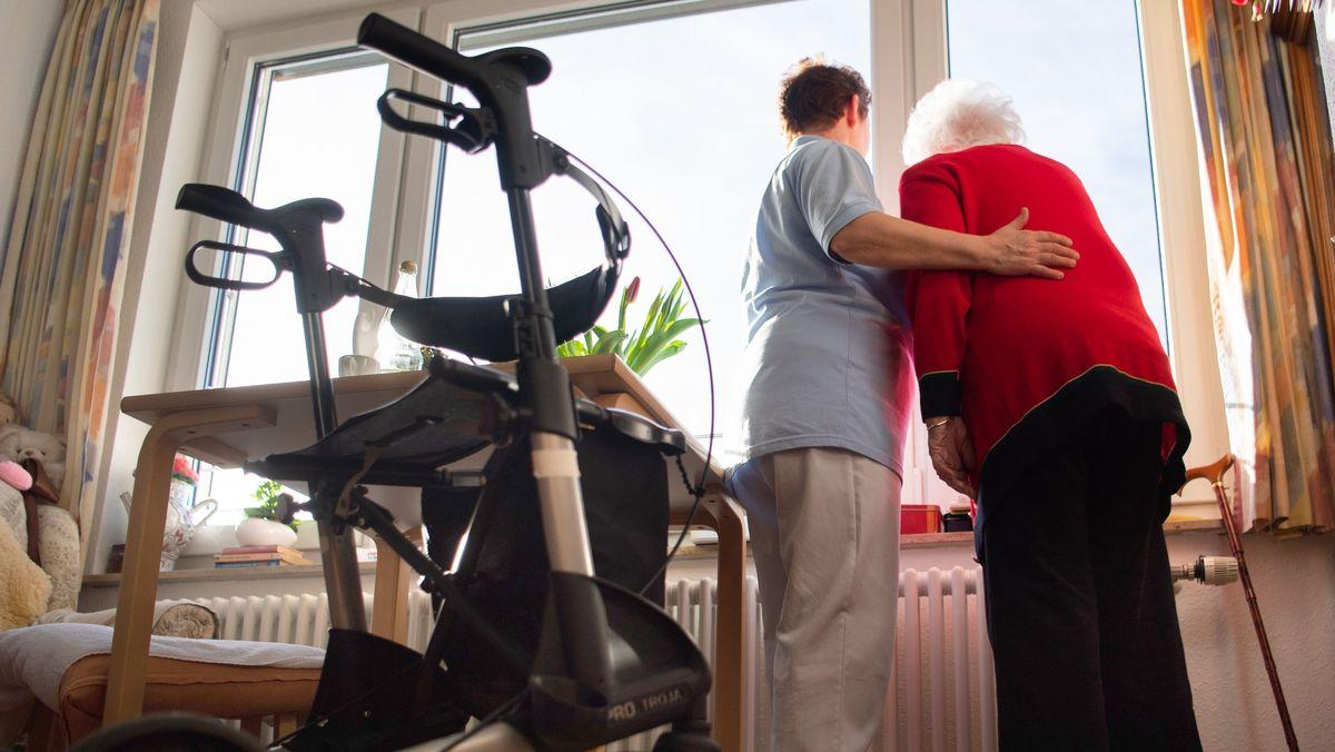 Eine Pflegerin (l) und eine Pflegebedürftige schauen zusammen aus einem Fenster.