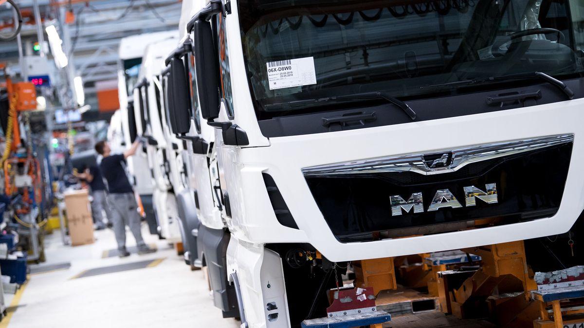 Mitarbeiter von MAN Truck & Bus arbeiten in einer Produktionsstraße.