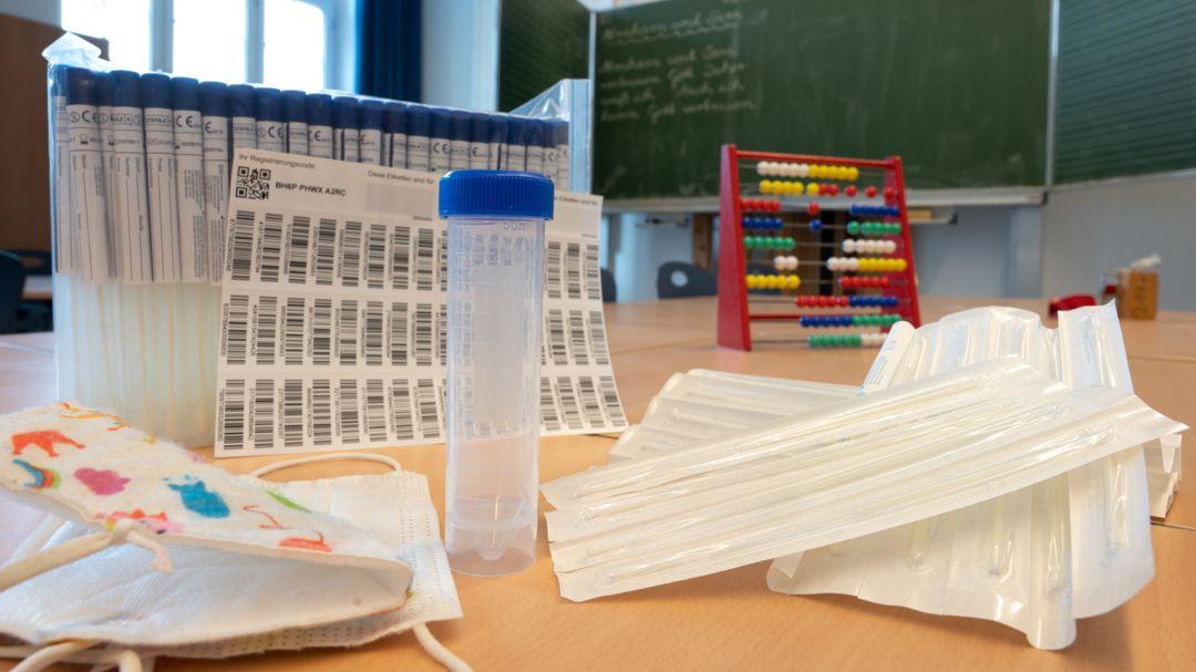 """Ein Set des sogenannten """"Lolli-Tests"""" (PCR-Pooltest) steht in einem Klassenzimmer"""
