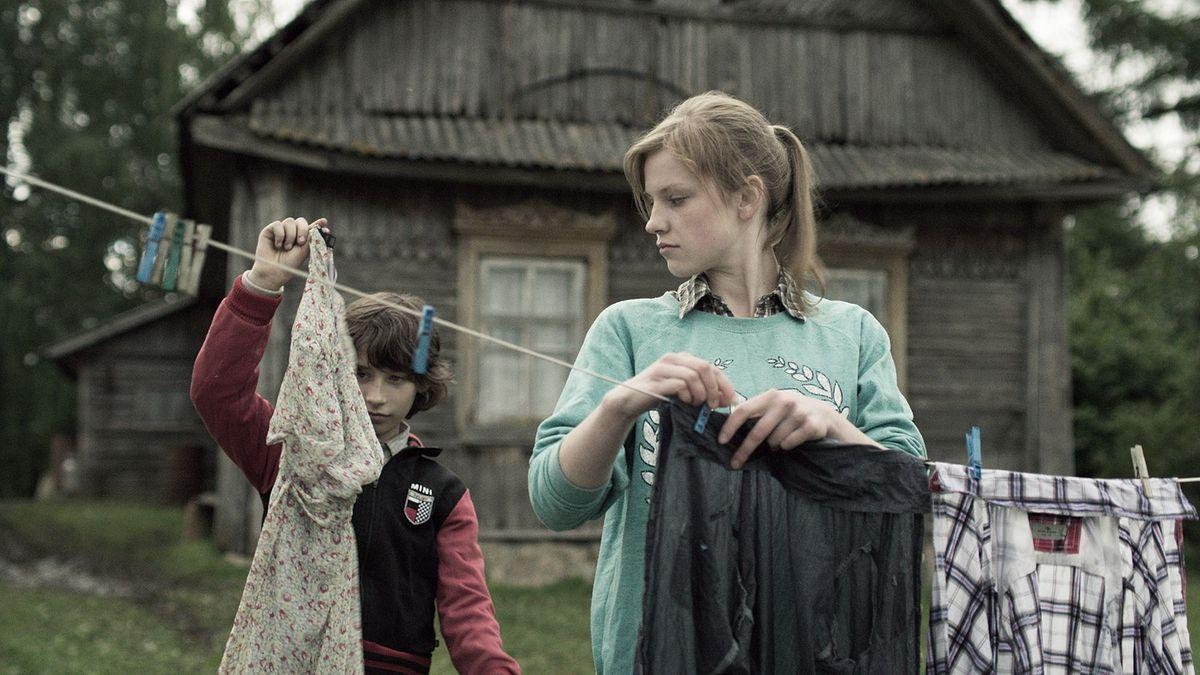 Bruder und Schwester hängen vor dem Holzhaus Wäsche auf einer Leine auf