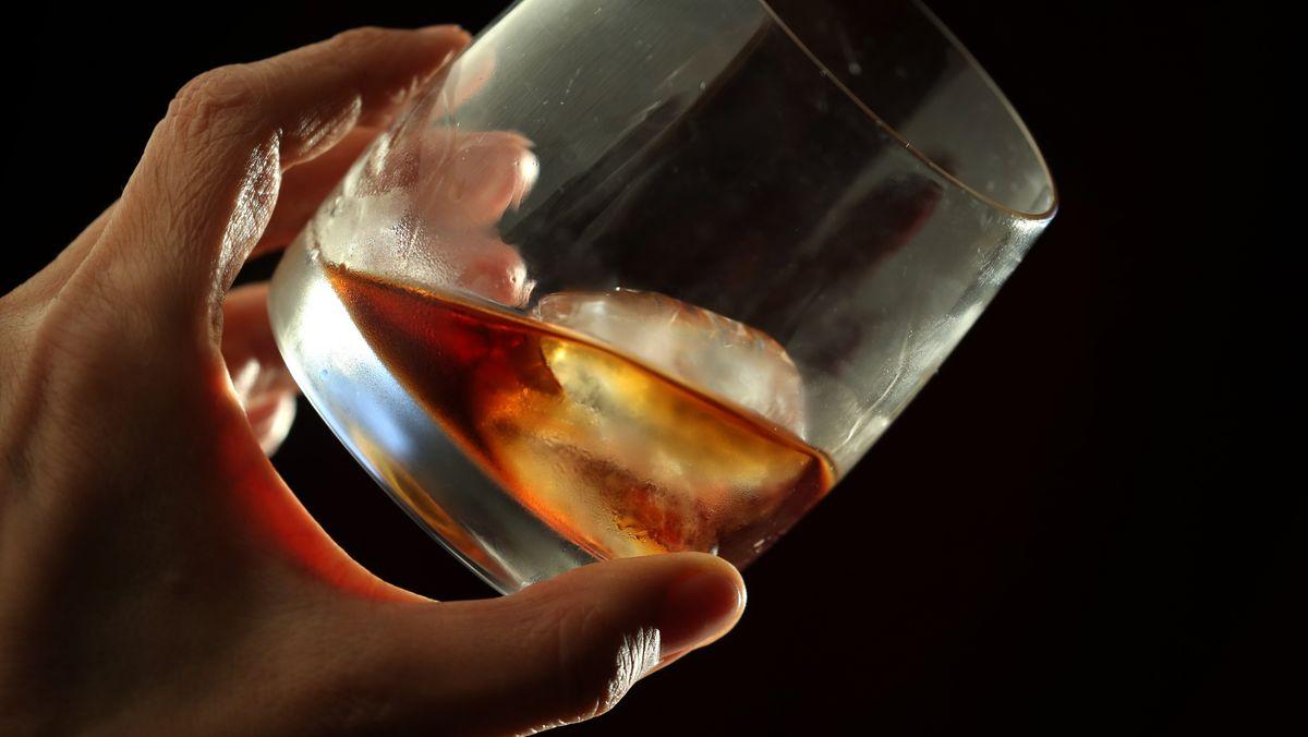 Eine Hand hält ein Glas, in dem sich Kräuterlikör und ein Eiswürfel befinden.