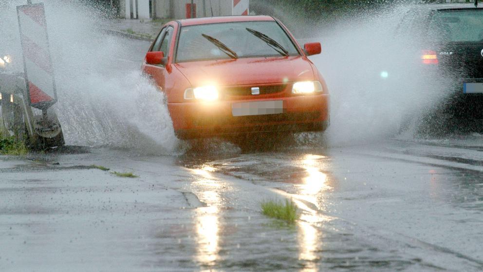 Wasser steht auf einer Straße (Symbolbild). | Bild:picture-alliance/dpa