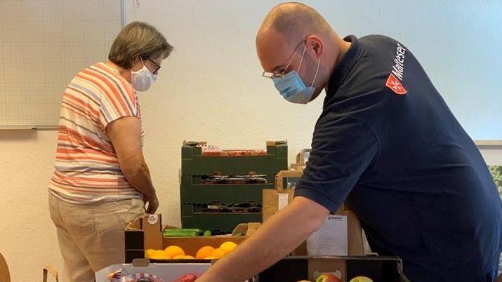 Malteser-Mitarbeiter in Neu-Ulm packen Brotzeittüten für Bedürftige mit frischem Obst