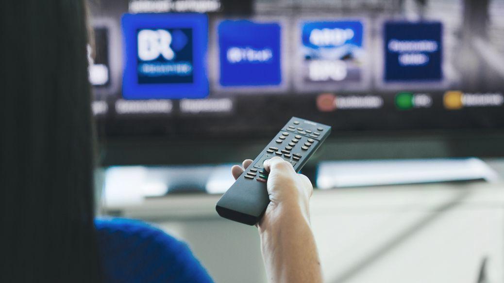 Eine Frau wählt mit der Fernbedienung das Programm der Mediathek auf dem Fernseher.