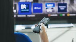 Eine Frau wählt mit der Fernbedienung das Programm der Mediathek auf dem Fernseher.   Bild:BR/Lisa Hinder