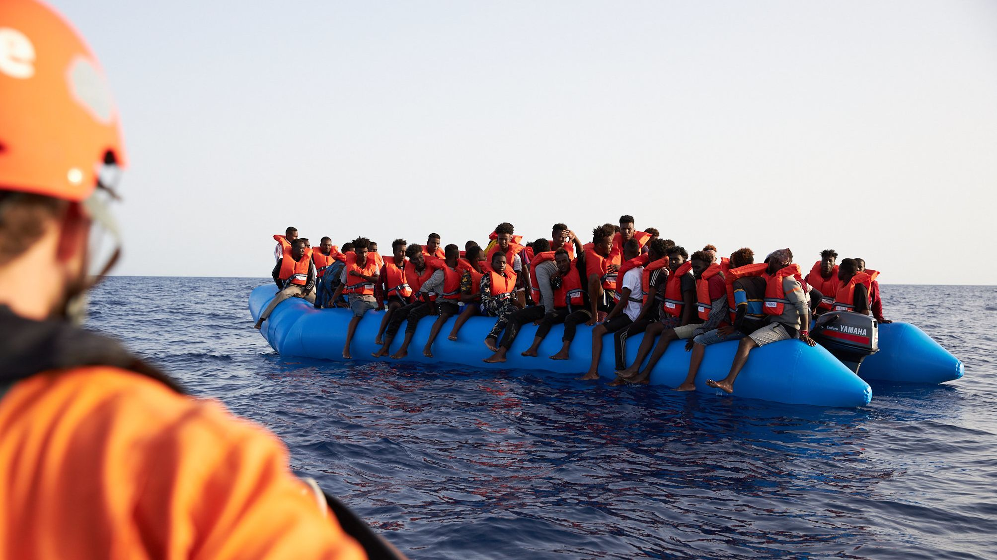 Die von der Seenotrettungsorganisation Sea-Eye herausgegebene Aufnahme zeigt einen Seenotretter der zu einem Flüchtlingsboot schaut.