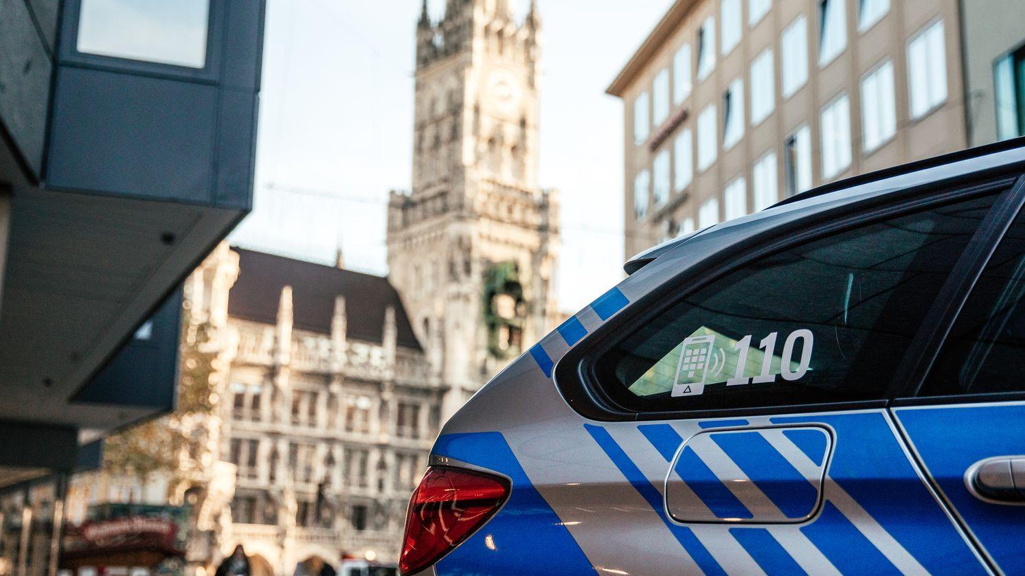 Am Münchner Marienplatz steht ein Polizeiauto mit einem Aufkleber an der Scheibe, der auf die Notrufnummer 110 hinweist.