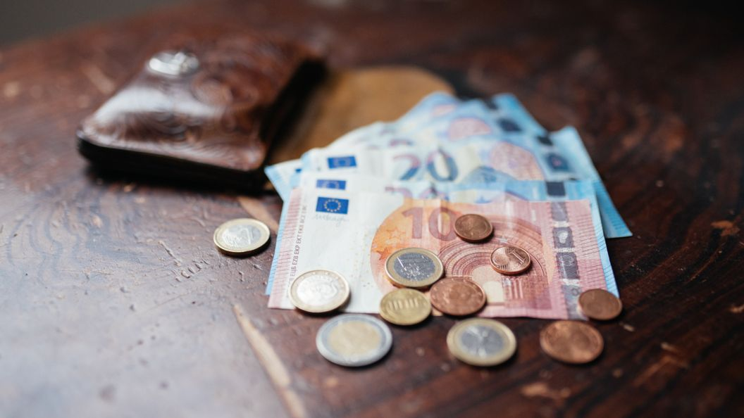Münzen und Geldscheine liegen auf einem Tisch.