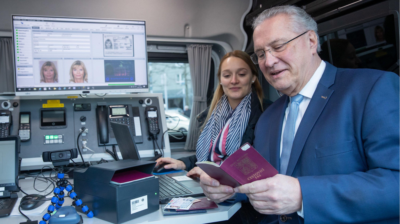 Hannah Pauli, Mitarbeiterin der Grenzpolizei Passau, demonstriert Joachim Herrmann (CSU), Bayerischer Innenminister, während der Vorstellung der Jahresbilanz 2019 der bayerischen Grenzpolizei in einem Basisfahrzeug der Polizei den mobilen Kontrollvorgang mit einem Dokumentenprüfgerät.