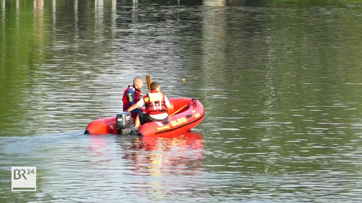 Zwei Rettungskräfte sitzen in einem roten Schlauchboot.