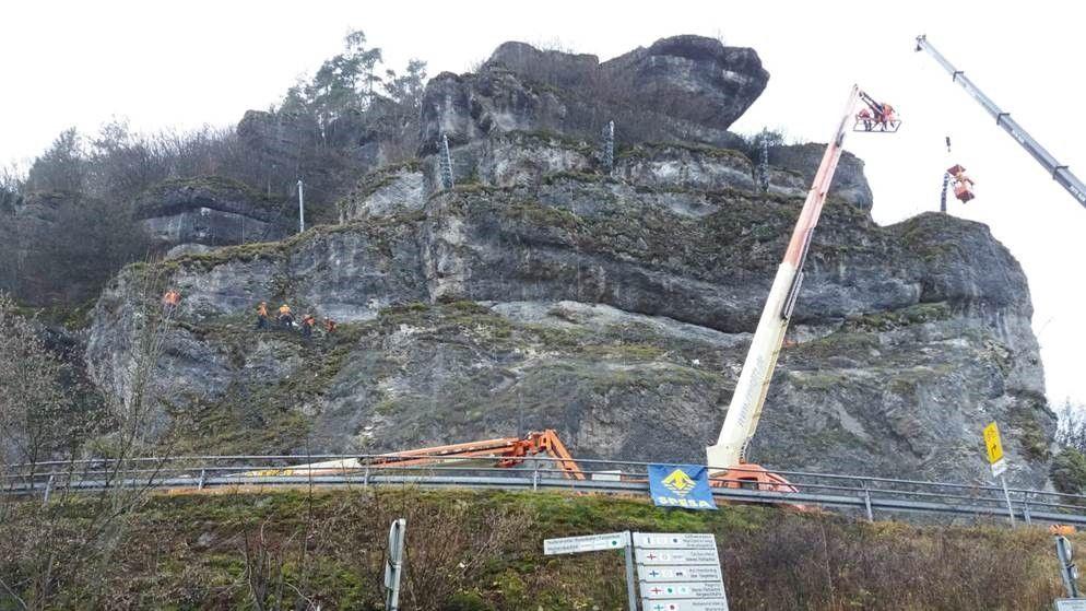 Kräne heben Stahlträger etwa 20 Meter hoch auf einen Hang, wo sie von einer Spezialfirma befestigt werden.