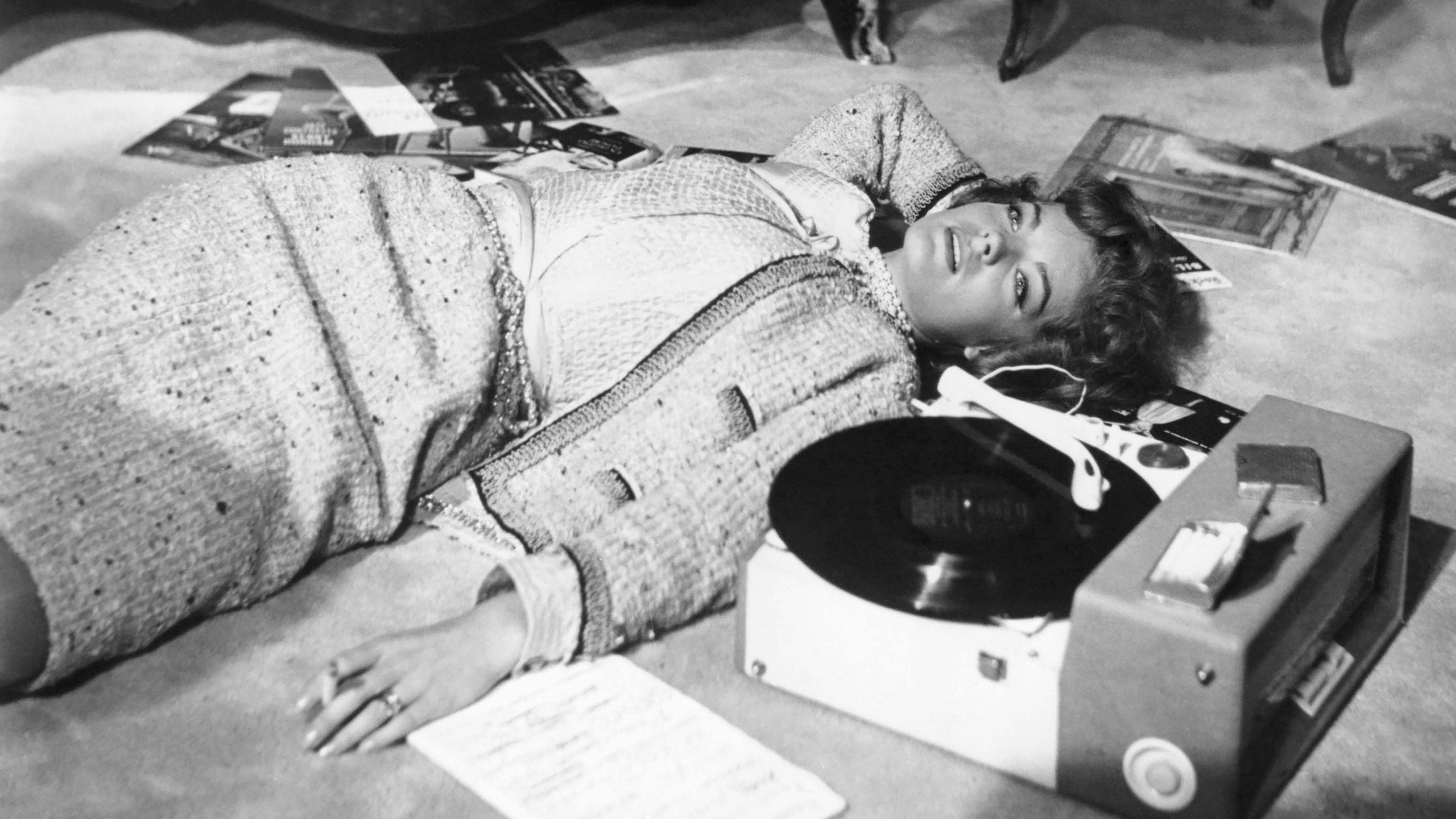 Romy Schneider liegt im Kostüm auf dem Boden neben einem Plattenspieler