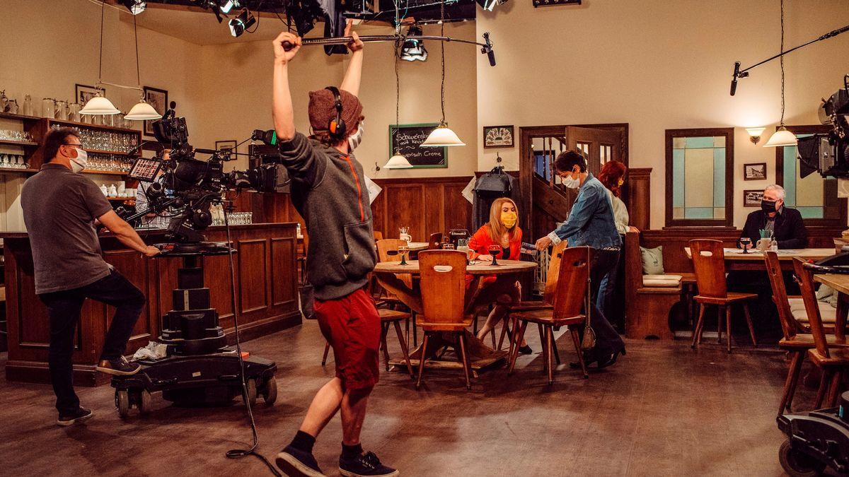 Filmset in einer Wirtschaft: Schauspielerin Silke Popp sitzt mit Mundschutz am Tisch, um sie herum Kameramann, Ton und Regie mit Mundschutz