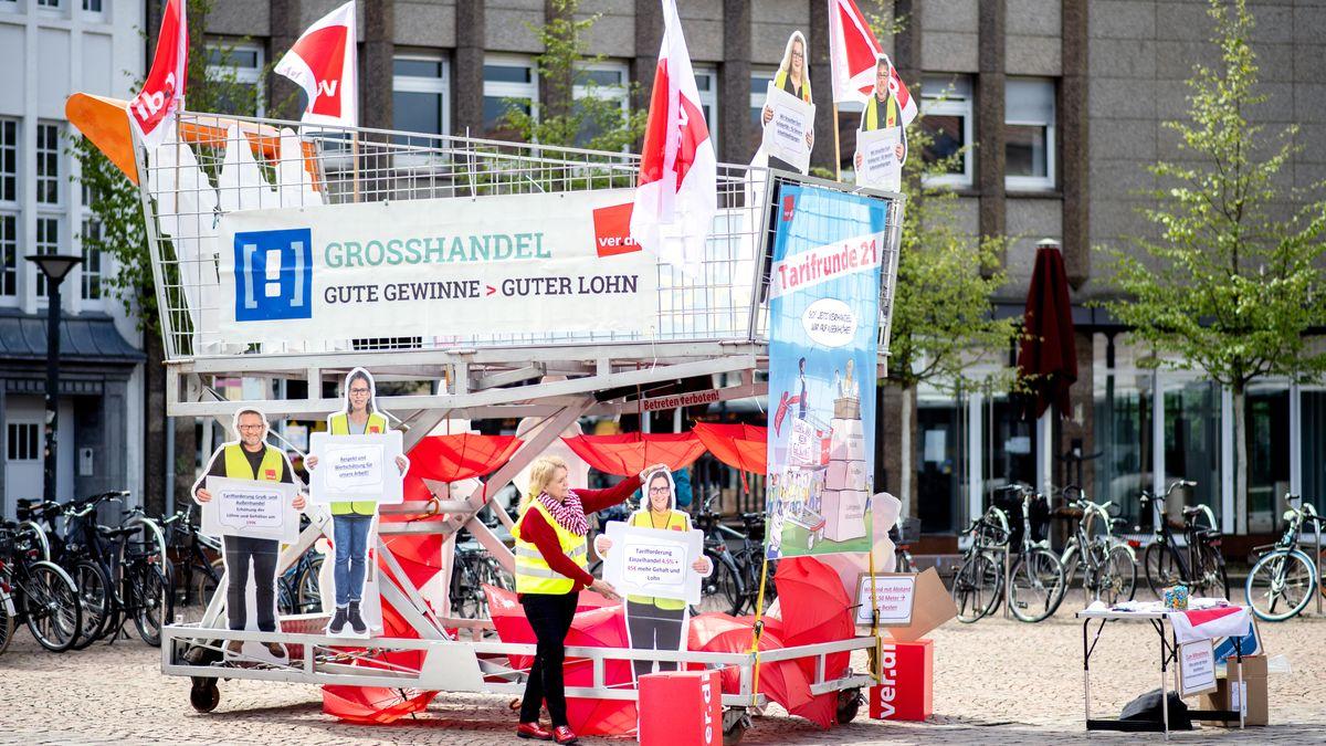 Eine Mitarbeiterin der Gewerkschaft Verdi im Fachbereich Handel, befestigt während einer Aktion zum Start der Tarifrunde für den Einzel- und Versandhandel mehrere Schilder an einem überdimensionalen Einkaufswagen im Stadtzentrum.