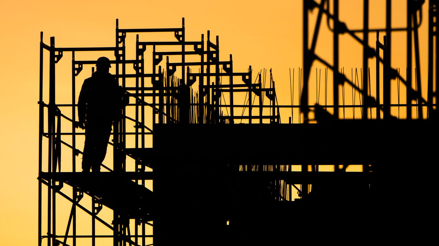 Ein Arbeiter steht auf einem Gerüst auf einer Baustelle.