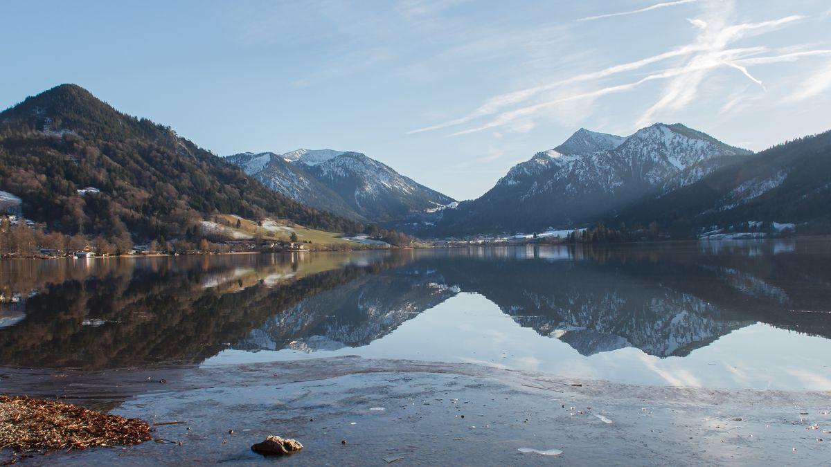Blick über den Schliersee, im Vordergrund das Ufer mit leichtem Eis-Überzug, im Hintergrund die leicht verschneiten Berge Brecherspitz und Jägerkamp
