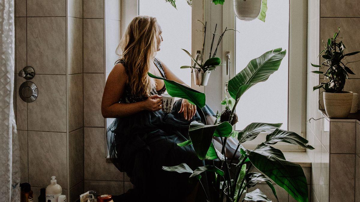 Frau in einem Badezimmer bei der Pflanzenpflege